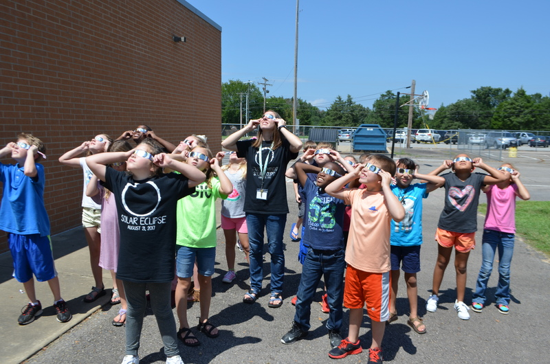 Third Grade students look at the solar eclipse with their teacher.